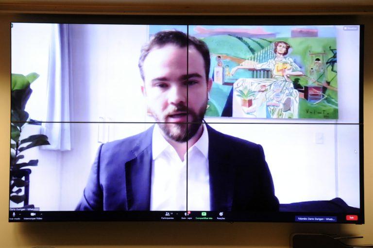 Dario Urigan fala olhando para a tela do computador. Ele é branco e usa barba