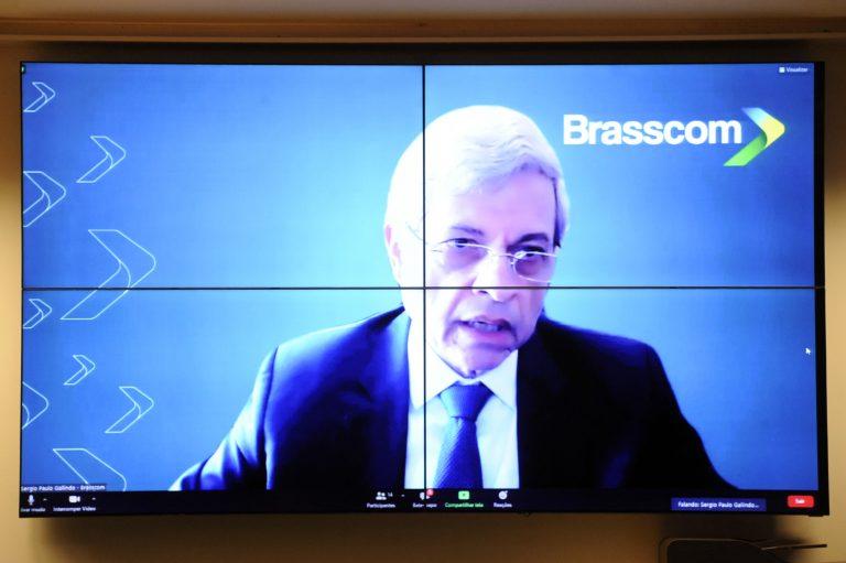 Sergio Gallindo fala olhando para a tela do computador. Ele é branco, veste um terno escuro e usa óculos
