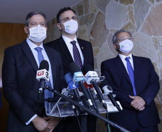 Presidentes da Câmara, Arthur Lira, e do Senado, Rodrigo Pacheco, esrão em pé ao lado do ministro da Economia. Todos usam terno e máscara