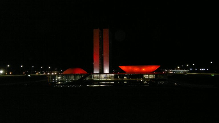 Prédio do Congresso iluminado de vermelho. Ao fundo a noite escura