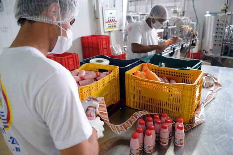 Dois homens trabalham embalando sucos caseiros. Eles vestem aventais, toucas e máscaras brancos. Em cima da mesa há garrafas de sucos e etiquetas