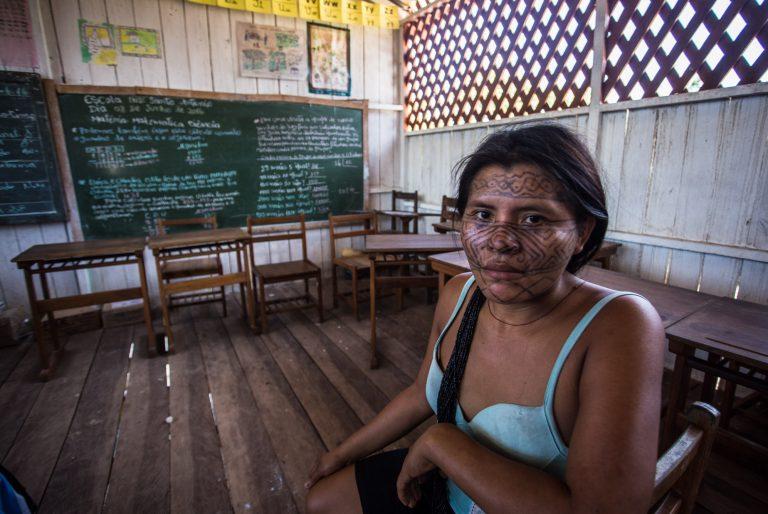 Uma índia com o rosto pintado está sentada numa sala de aula. Ao fundo, há um quadro negro com coisas escritas.