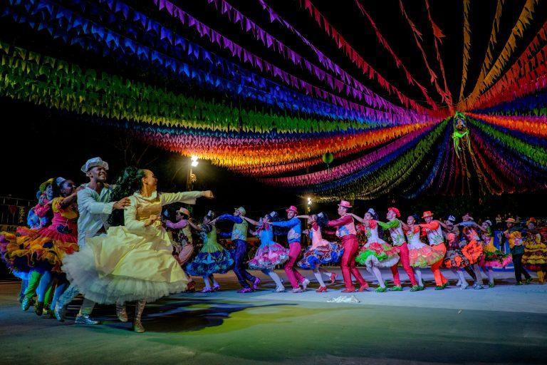 Pessoas danção quadrilha de São João com roupas típicas, em pátio enfeitado com bandeirolas coloridas