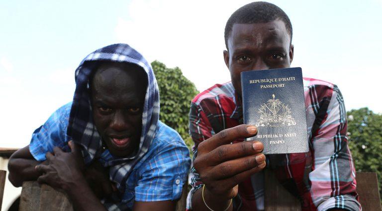 Dois homens negros vindos do Haiti seguram seus passaportes