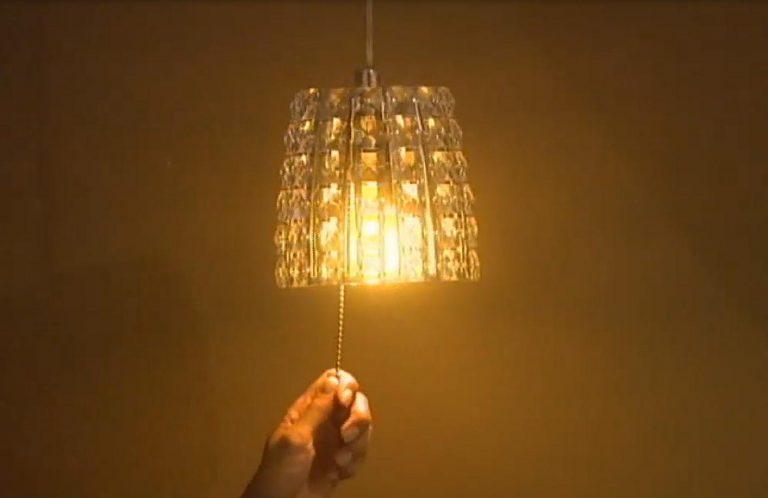 Foto de uma mão puxando uma cordinha para acender um lustre