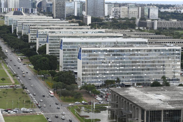 Vista aérea da Esplana dos Ministérios em Brasília. Vários prédios altos com muitas janelas, uma rua larga na frente e um amplo gramado