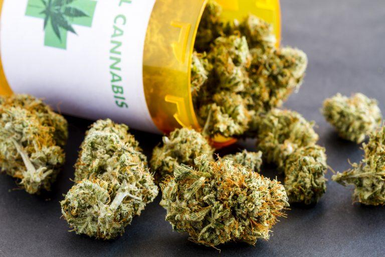 Em cima da mesa há um pote aberto de onde caem folhas secas de Cannabis
