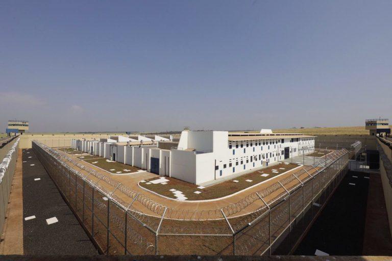 Prédio de penitenciária. Construção branca de vários andares cercada por cercas e muros