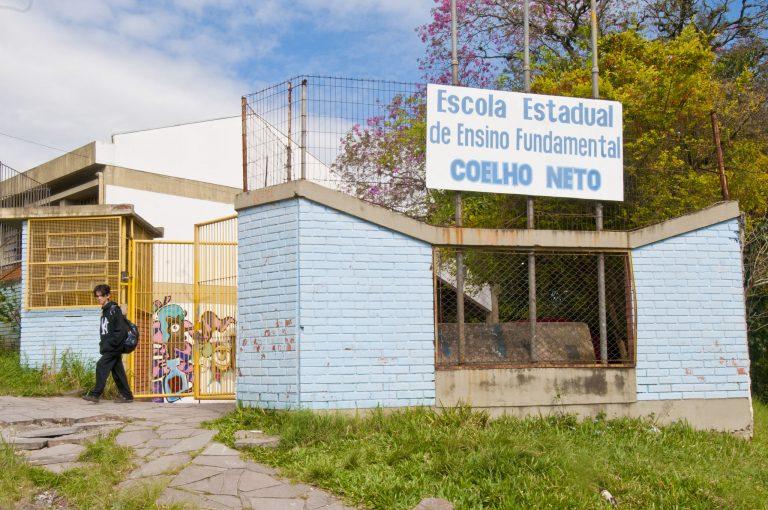 Facahada de uma escola pública. Um muro branco com portões amarelos