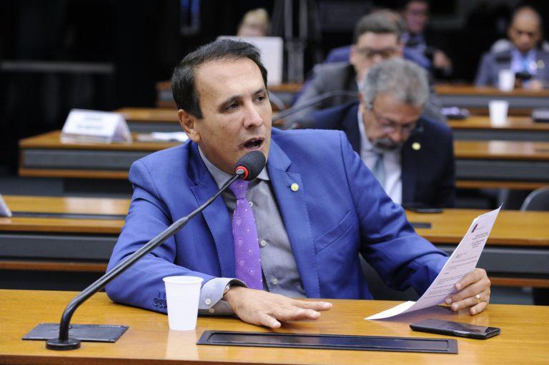Deputado Carlos Henrique Gaguim está sentado falando ao microfone. Ele usa um terno azul escuro e segura um papel