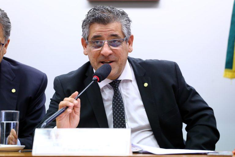 Deputado Nereu Crispim está sentado falando ao microfone