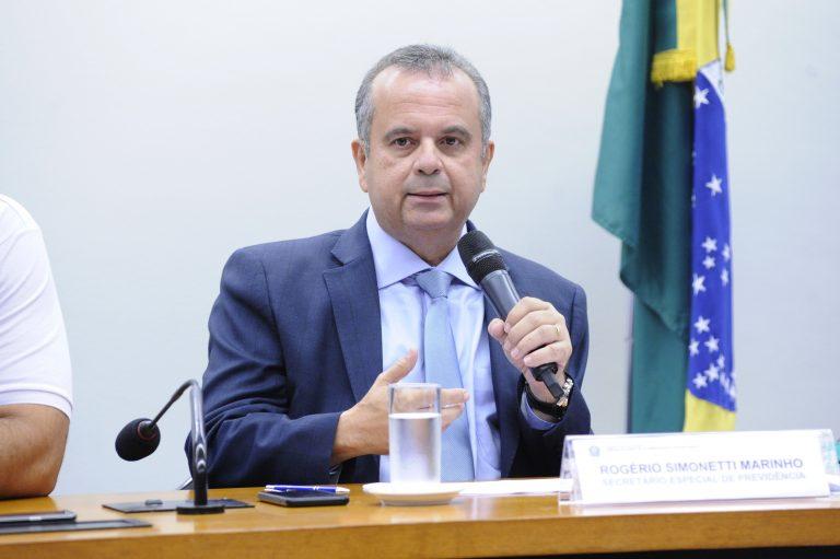 Ministro Rogério Marinho está sentado falando ao microfone