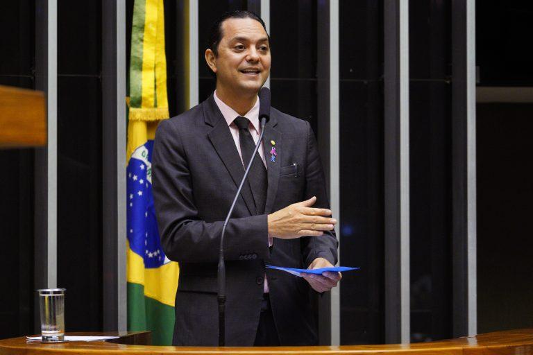 Deputado Weliton Prado discursa no Plenário da Câmara. Ele veste um terno escuro e segura um papel. Ao fundo, à esquerda há uma bandeira do Brasil