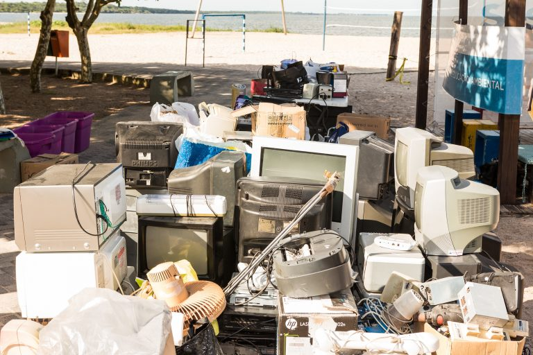 Vários equipamentos eletrônicos estão amontoados em cima de uma calçada