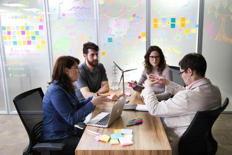 Um grupo de pessoas está sentado à mesa trabalhando. Há um laptop e papéis sobre a mesa