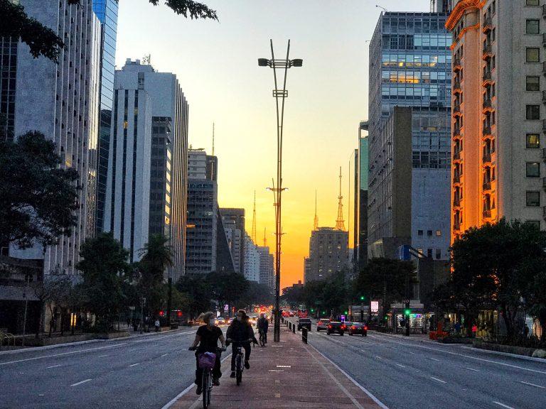 No centro da foto há uma ciclovia, aos lados avenidas com carros e mais ao fundo arranha-céus