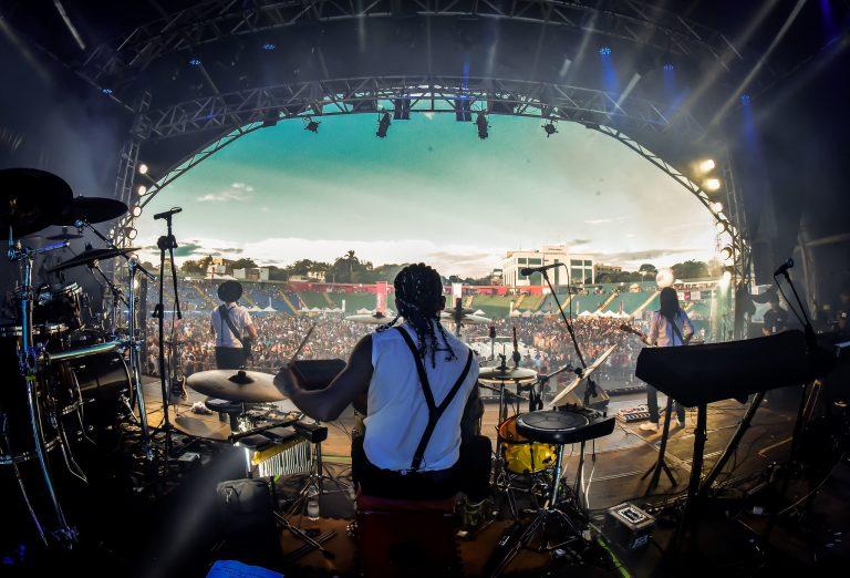 Show de banda de música. Foto do palco mostra os artistas e ao fundo a plateia num estádio aberto