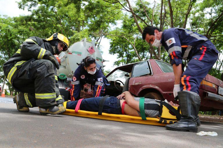 Um homem está deitado numa maca numa rua sendo socorrido por bombeiros