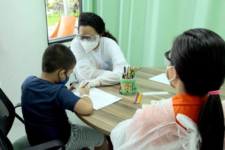 Criança está sentada de costas escrevendo numa folha. Duas mulheres estçao sentadas à mesa com ela. Todos usam máscara facial