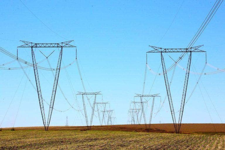 Torres de transmissão de energia elétrica num descampado. Ao fundo o céu azul