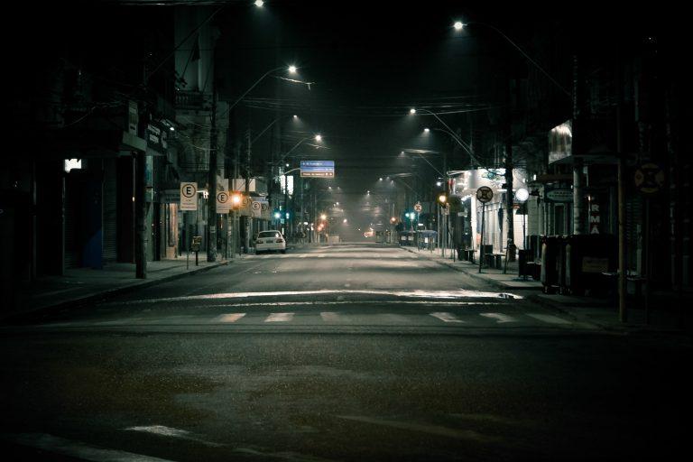 Rua escura com postes acesos.