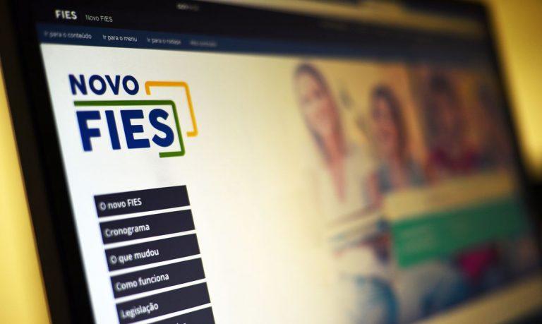 Tela de computador aberta no site do Fies. Em primeiro plano está escrito Novo Fies e ao fundo há uma imagem desfocada de alguns alunos