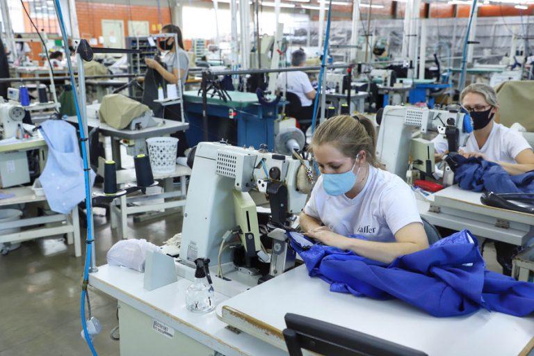 Mulheres costuram numa indústria