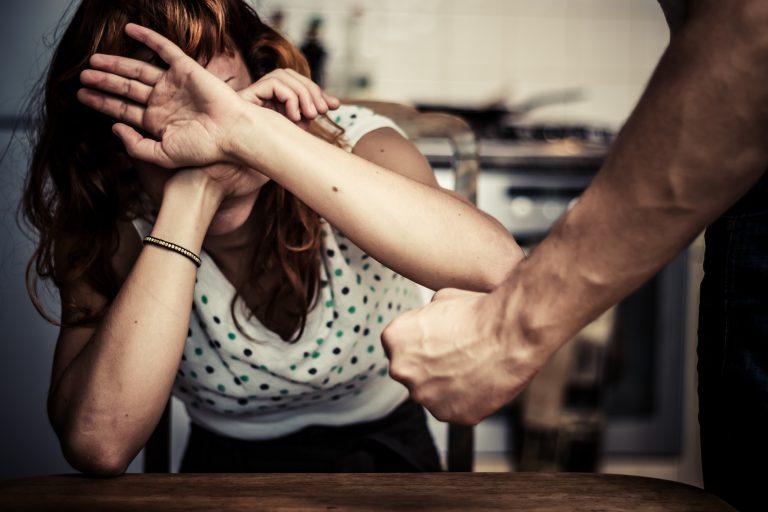 Uma mulher esconde o rosto com as mâos para se defender de um homem com os punhos cerrados