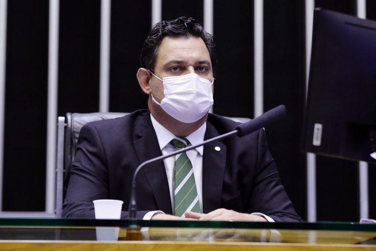 Deputado Geninho Zuliani está sentado atrás de um microfone. Ele usa máscara facial e um terno escuro