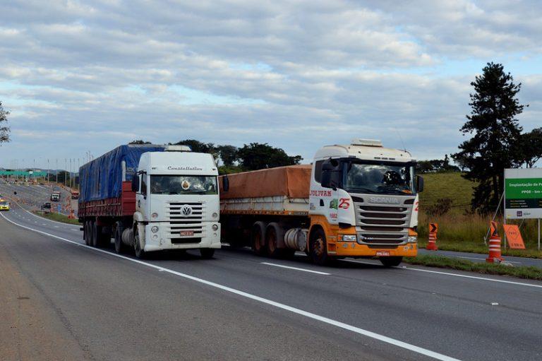 Dois caminhões trafegam numa rodovia