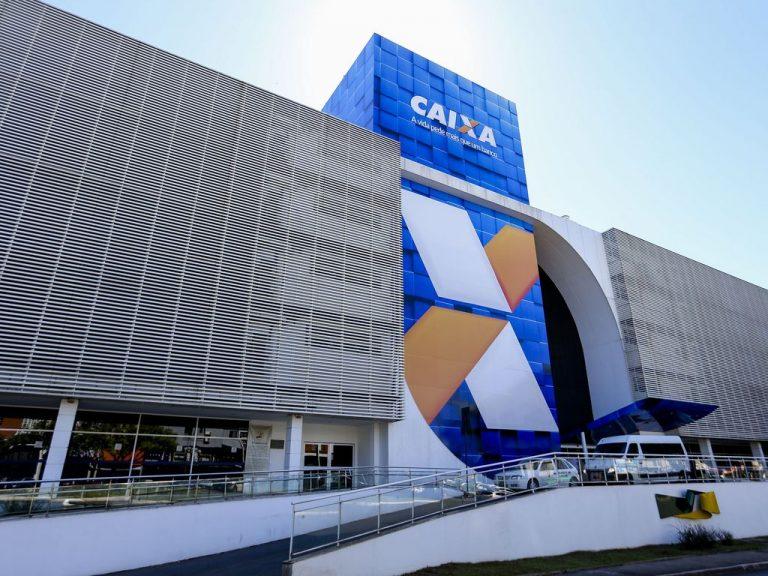 Fachada de um prédio cinza e azul com a logomarca da Caixa Econômica