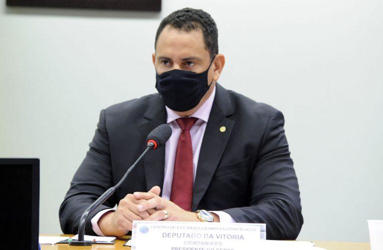 Deputado Da Vitoria está sentado falando ao microfone. Ele usa terno escuro e máscara facial