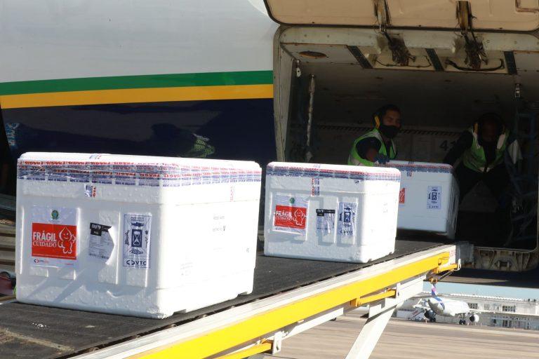 Caixas de isopor com vacinas contra a Covid-19 estão numa esteira para serem carregadas num avião