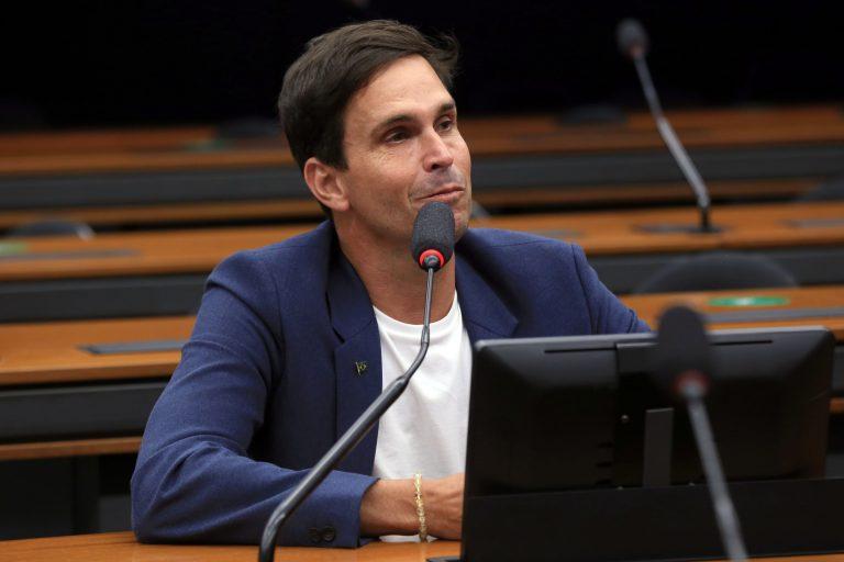 Deputado Luiz Lima está sentado falando ao microfone