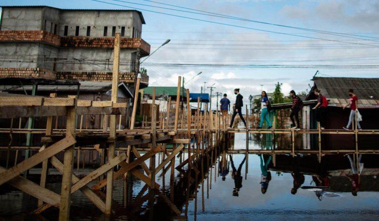 Pessoas caminham em pontes sobre região alagada