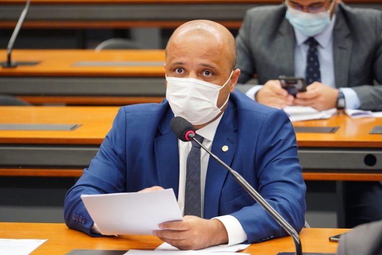Deputado Vitor Hugo está sentado de máscara e segura um papel nas mãos