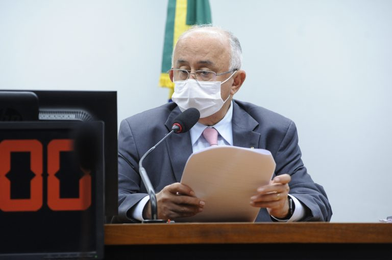 Deputado Júlio Cesar está sentado falando ao microfone. Ele usa máscara e segura um papel