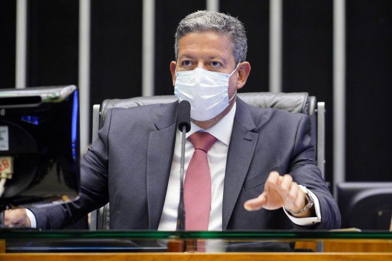 Presidente da Câmara, Arthur Lira, está sentado de máscara, falando ao microfone