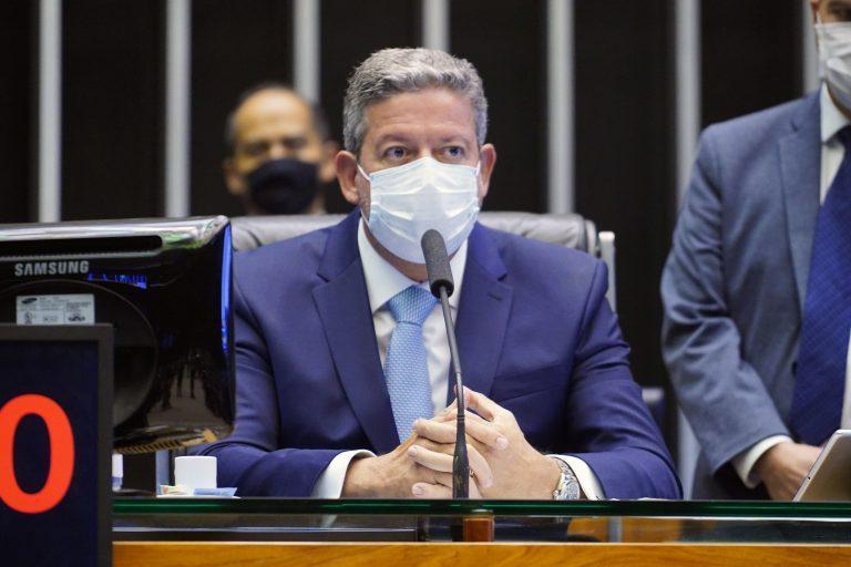 Presidente da Câmara, deputado Arthur Lira, está sentado e fala ao microfone. Ele usa máscara e veste um terno azul marinho
