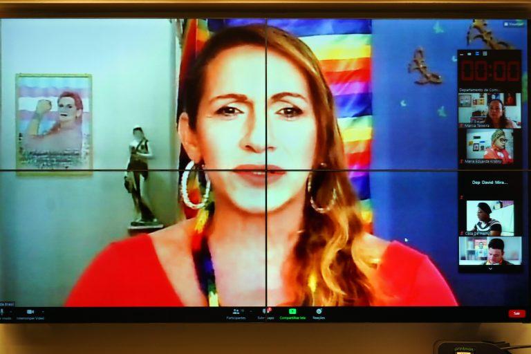 Mulher loira de blusa vermelha fala olhando para a tela do computador. Atrás dela há uma bandeira com as cores do arco-íris em uma parede azul