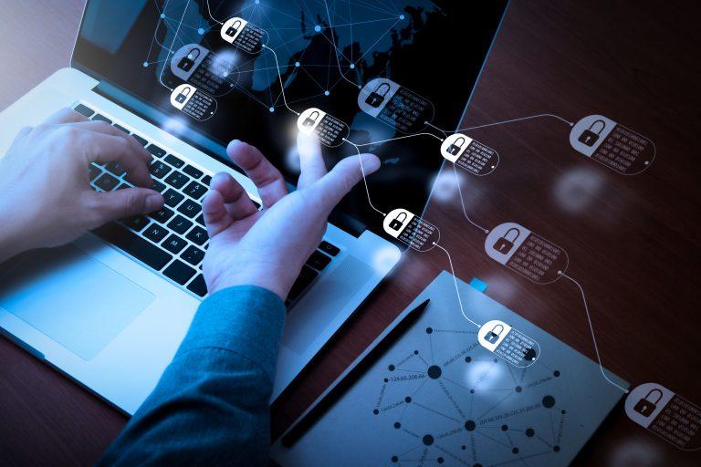 Um laptop com vários ícones de cadeados e uma pessoa com o indicador num desses ícones