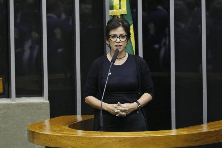 Deputada Alê Silva discursa no Plenário. Ela veste preto e usa óculos