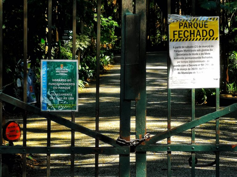 """Portão de parque público fechado por causa da pandemia. Na grade verde está afixado um cartaz onde se lê: """"Parque fechado"""""""