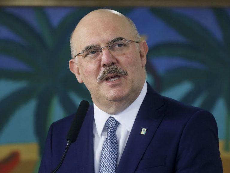 Ministro da Educação, Milton Ribeiro, usa um terno escuro, bigode e óculos. Ele é calvo e está diante de um fundo azul escuro