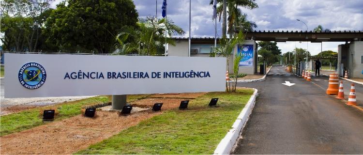 Entrada da Agência de Inteligência Brasileira. Uma rua leva a uma guarita e à esquerda há uma placa com o nome da agência