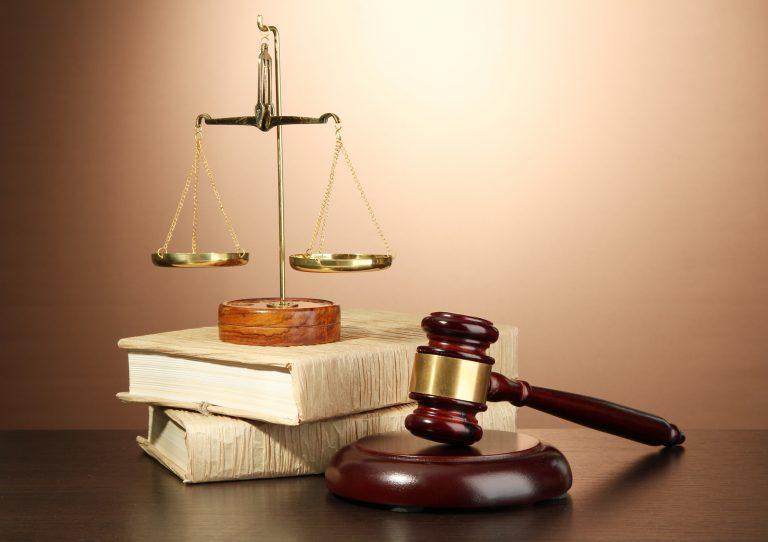 Uma balança está em cima de dois livros empilhados. Ao lado há um partelo de juiz.