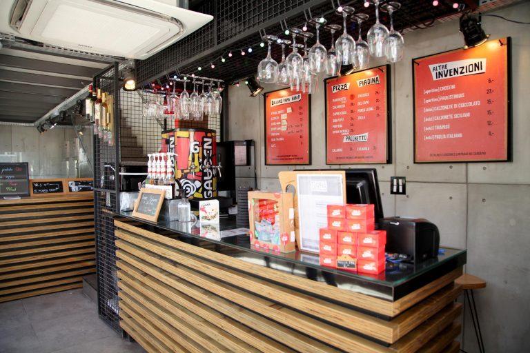 Foto do balcão de um restaurante. A bancada é de madeira, a parede é cinza e há copos pendurados num suporte em cima do balcão