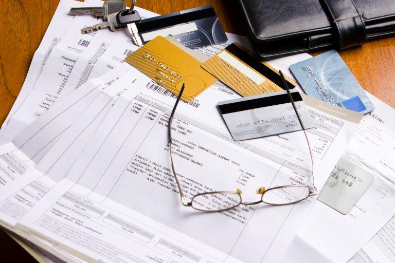 Em cima da mesa há vários boletos, cartões e um óculos