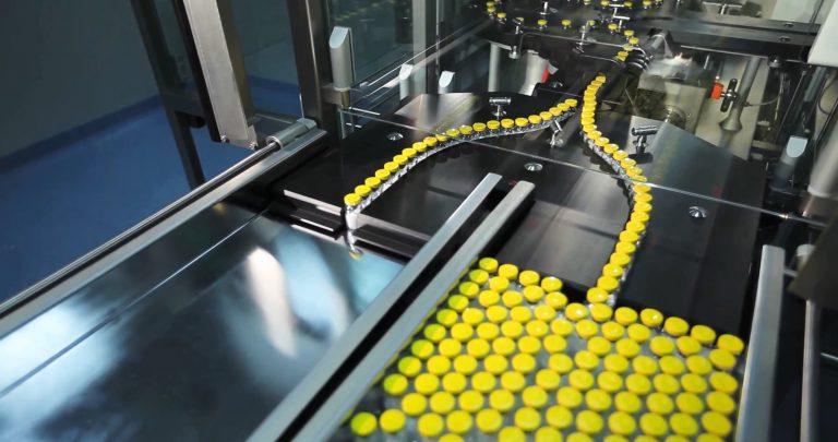 Vários frascos de medicamentos com tampa amarela estão na esteira de um equipamento numa fábrica