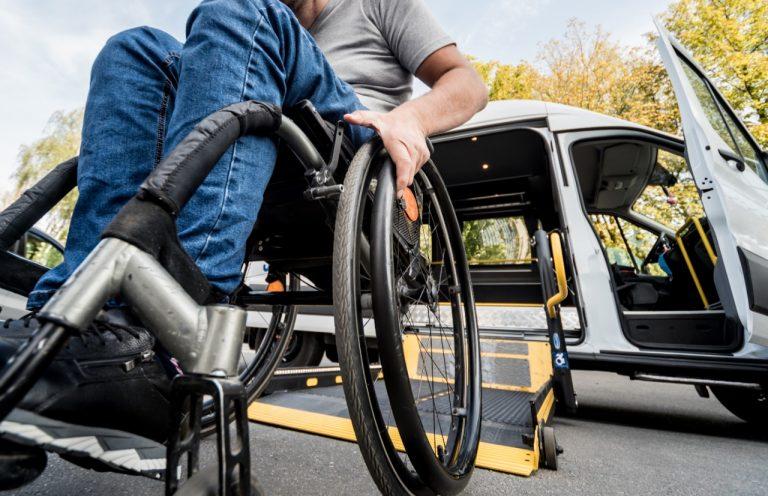 Uma pessoa em cadeira de rodas embarca um carro adaptado